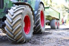 Grön och röd traktor med stora hjul och den selektiva fokusen Traktor på ett konstruktionsområde Arkivbild