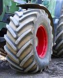 Grön och röd traktor med stora hjul och den selektiva fokusen Traktor på ett konstruktionsområde Arkivbilder