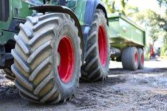 Grön och röd traktor med stora hjul och den selektiva fokusen Traktor på ett konstruktionsområde Royaltyfri Fotografi