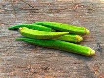 Grön okra för friskhet på gammal trätabell- och träbakgrund Royaltyfri Fotografi