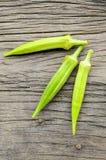 Grön okra på trägolvet, abelmoschus esculentus Fotografering för Bildbyråer