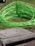 Grön optisk kabel för fiber som travas av bostads- hus på förort av adelsmannen, parkerar framme Arkivbilder
