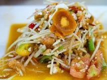 Grön papayasallad eller Somtum med det bevarade ägget Populär thailändsk lokal mat Kryddig sallad från den strimlade omogna papay Royaltyfri Bild