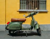 Grön Piaggio Vespa LML T5 150 som parkeras på sida av gatan med gul bakgrund Arkivbilder