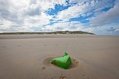 Grön plast- avskräde på den holländska stranden av Vlieland Arkivbild