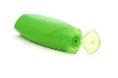Grön plast- schampoflaska med det öppnade flipöverkantlocket Arkivbild