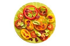 Grön platta av sallad med skivade tomater på vit Royaltyfria Foton