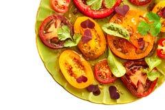 Grön platta av sallad med skivade tomater på vit Fotografering för Bildbyråer