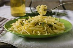 Grön platta med spagetti och den hängande gaffeln Royaltyfria Bilder