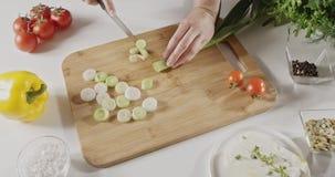 Grön purjolök för kvinnaskivor för salladförberedelsen med en kniv på att klippa träbrädet på ett vitt köksbord Top beskådar stock video