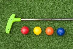 Grön puttputtklubba med bollar Fotografering för Bildbyråer