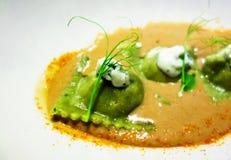 Grön ravioli i kryddig sås med ärtagroddar royaltyfria foton