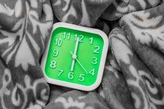 Grön ringklocka på sängen Det alarmerar på 6 00 ägaar rum på arbetsdag tim Arkivfoto