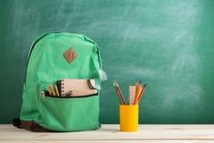grön ryggsäck, anteckningsböcker och skolatillförsel på bakgrunden av svart tavla royaltyfri foto