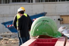 Grön säkerhetshardhat på förgrund Byggnadsarbetare på bakgrund arkivbilder