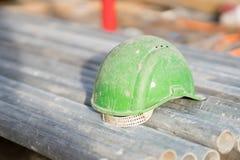 Grön säkerhetshjälm på metallrör royaltyfria bilder