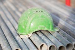 Grön säkerhetshjälm på metallrör arkivfoto