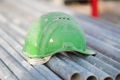 Grön säkerhetshjälm på metallrör fotografering för bildbyråer