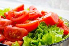 Grön sallad och skivade tomater Arkivfoto