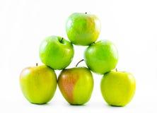 Grön sex och gula äpplen som bildar en pyramid på en vit bakgrund Arkivfoton