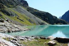 Grön sjö i berg, Tien Shan Arkivfoto