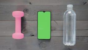 Grön skärm - en Smartphone, vattenflaska och en hantel på en tabell lager videofilmer