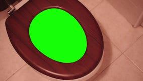 Grön skärm inom vattenklosetten som öppnas av en hand arkivfilmer