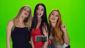 grön skärmstudio Modellen för tre flicka poserar för selfiefoto arkivfilmer