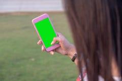 Grön skärmtelefon i händerna av flickan royaltyfria foton