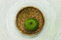 Grön skein av ull i brun korg Fotografering för Bildbyråer