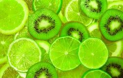 Grön skiva av limefrukt- och kiwibakgrund Arkivbilder