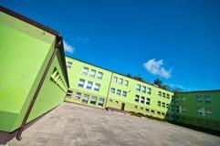 Grön skolabyggnad arkivfoton
