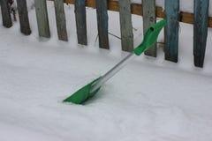 Grön skyffel för snöborttagning i gården av ett privat hus gör ren banan på ingången till porten i snöig vinter royaltyfria foton