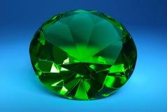 Grön smaragd på ett mörker - blå bakgrund. Arkivbild