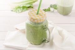 Grön smoothie i en glass krus med locket och ett sugrör Royaltyfri Bild