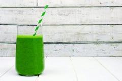 Grön smoothie i ett exponeringsglas med sugrör över vitt trä Arkivbilder