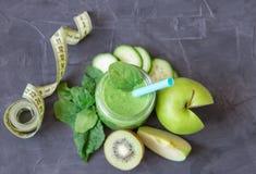 Grön smoothie med ingredienser: äpplen, spenat, gurka och kiwi med måttbandet banta äta som är sunt arkivfoto