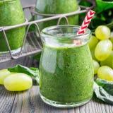 Grön smoothie med spenat, druva och banan som garneras med hallon, fyrkantformat Arkivbilder