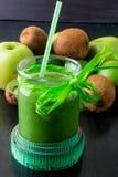 Grön smoothie nära cm och ingredienser för det på svart träbakgrund banta detox Sund drink Arkivbild