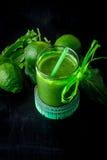 Grön smoothie nära cm och ingredienser för det på svart träbakgrund banta detox Sund drink Royaltyfria Foton