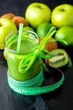 Grön smoothie nära cm och ingredienser för det på svart träbakgrund banta detox Sund drink Arkivfoton