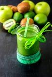 Grön smoothie nära cm och ingredienser för det på svart träbakgrund banta detox Sund drink Royaltyfri Foto