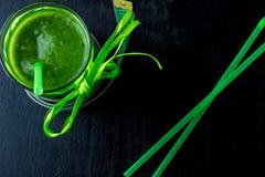 Grön smoothie nära cm på svart träbakgrund banta detox Sund drink Top beskådar Arkivfoto