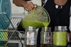 Grön smoothie och exponeringsglas Royaltyfri Foto