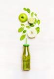 Grön smoothiedrink i flaska med sugrör och ingredienser (spenat, äpple, limefrukt) på vit träbakgrund Royaltyfri Bild