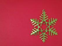 Grön snöflinga på rött Royaltyfri Fotografi