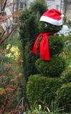 Grön snögubbe som bär ett röd lock och halsduk Arkivbilder