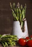 Grön sparris med tomater på brun bakgrund Royaltyfria Bilder