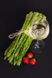 Grön sparris med vitt vin och jordgubbar Royaltyfri Foto