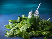 Grön spenatspirulinasmoothie i murarekrus Arkivfoton